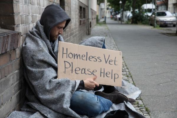 maennliche obdachlose sitzen auf einer strasse