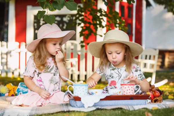 zwei kleine maedchen sitzen auf gruenem