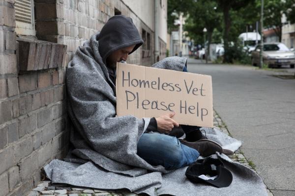 maennliches obdachloses sitzen auf einer strasse