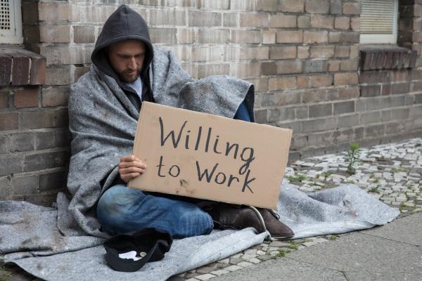 obdachloser mann haelt karton mit text