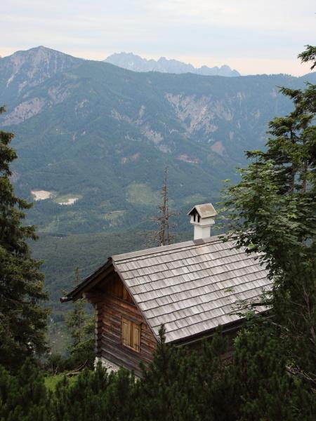 kleines wanderhaus auf klippenueberhang mit bergblick