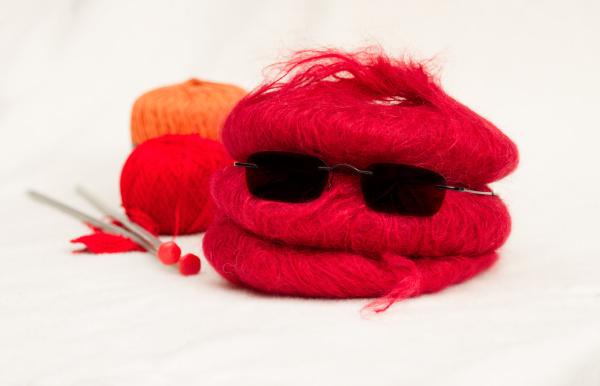 wolleknaeuel mit stricknadeln und sonnenbrille