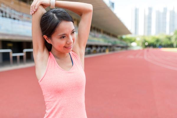 sportfrau die arm im sportkomplex ausdehnt