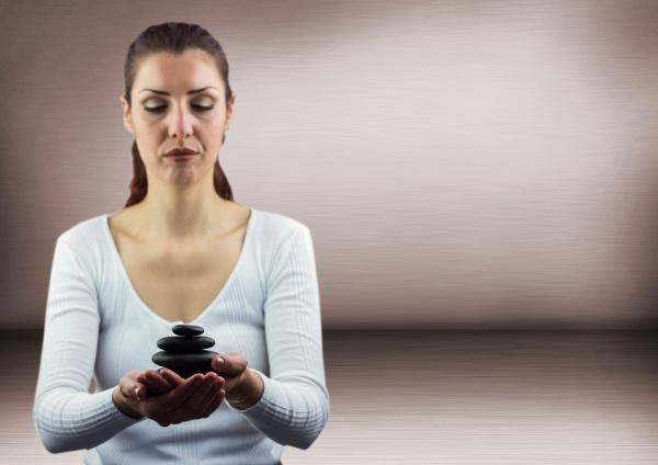 frau meditiert mit steinen gegen rosa