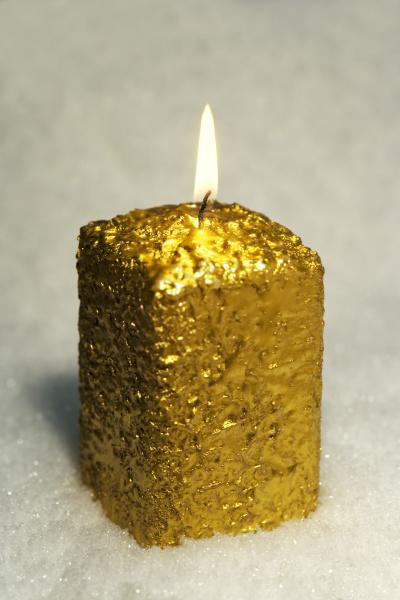 brennende goldene kerze im schnee
