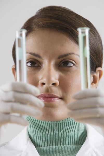 indischer weiblicher wissenschaftler der phiolen betrachtet