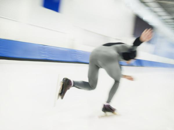 maennlicher geschwindigkeits skater der eislaeuft