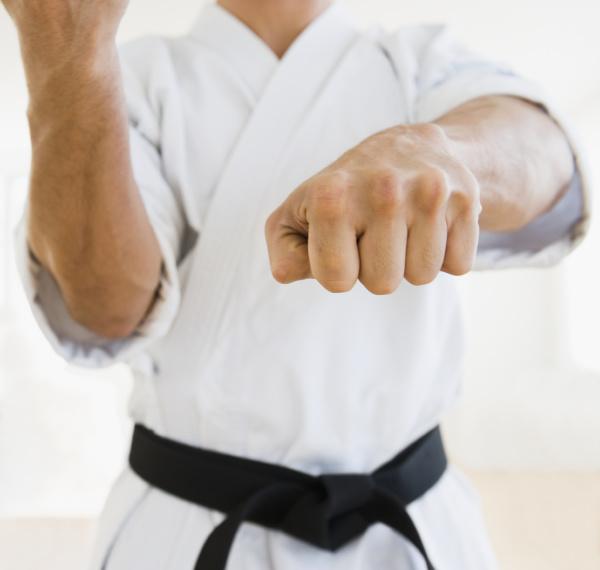 maennlicher karateschwarzgurt in kaempfender position