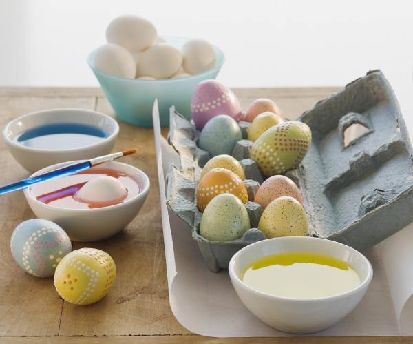 dekorierte eier neben schuesseln mit farbstoff