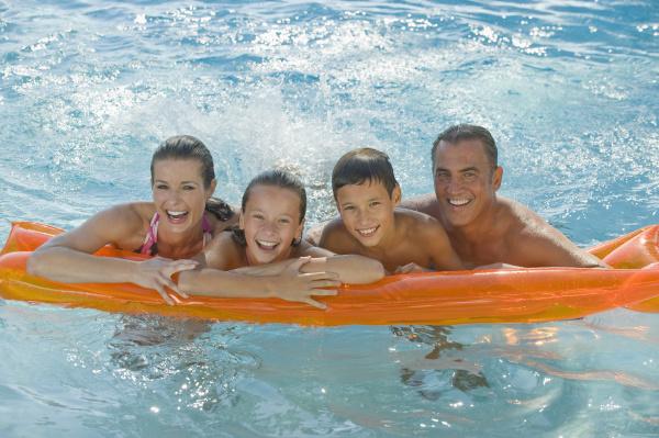 familie die auf floss im swimmingpool