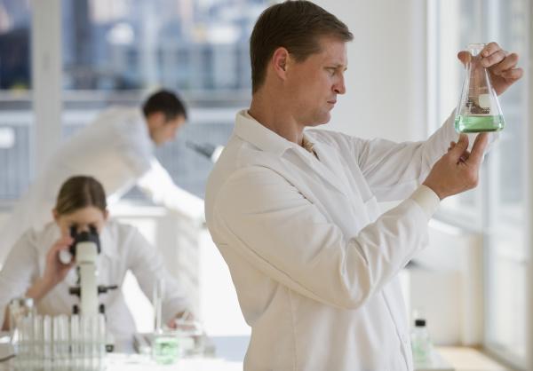 wissenschaftler untersucht fluessigkeit im pharmazeutischen labor