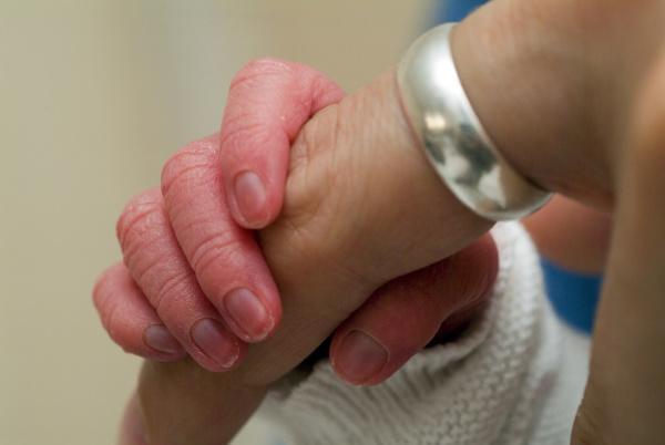 hand eines neugeborenen greift nach dem