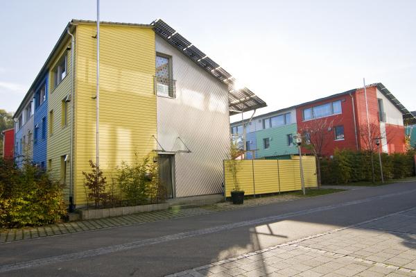 passivhauser mit solarzellen und bunter holzfassade
