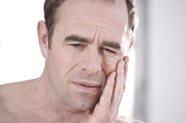 ein mann hat zahnschmerzen