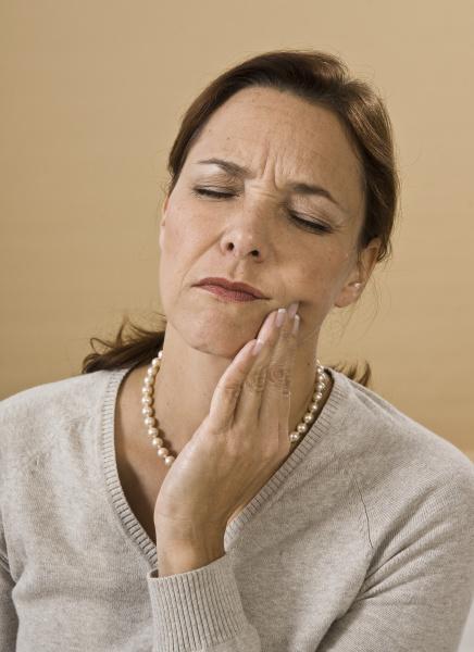 eine frau mit starken zahnschmerzen