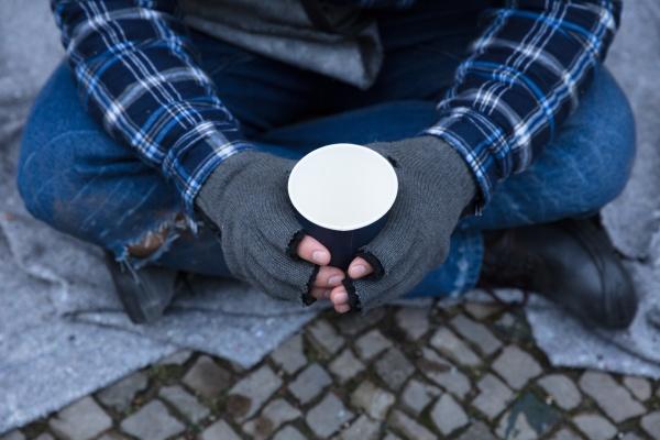 beggar holding einweg cup