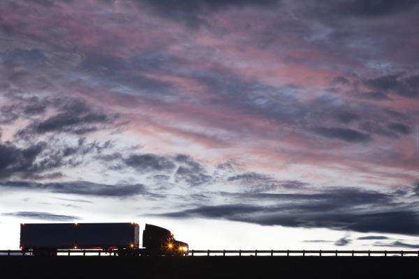 silhouette eines verkehrswagens der bei sonnenuntergang