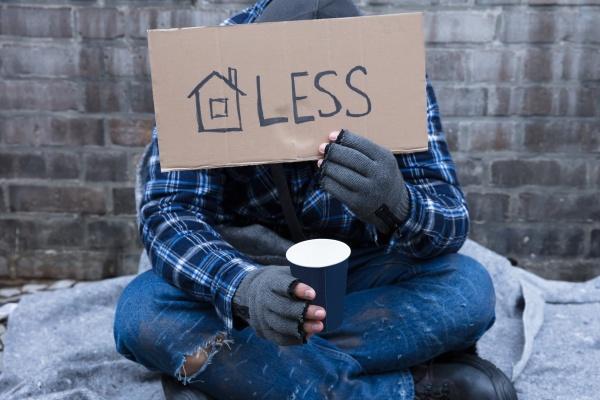 bettler der obdachloses plakat haelt