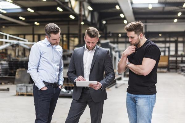 drei maenner teilen tablet auf fabrik