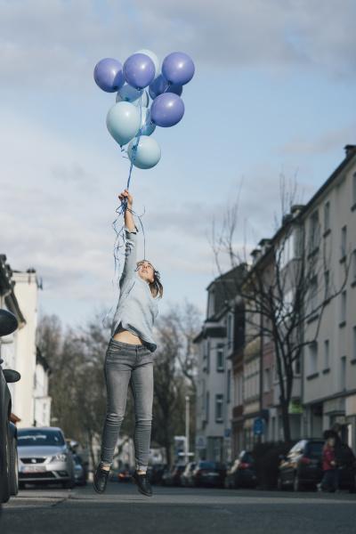 junge frau mit blauen luftballons springt