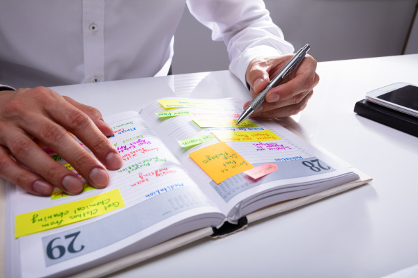geschaeftsmann schreibt zeitplan im tagebuch