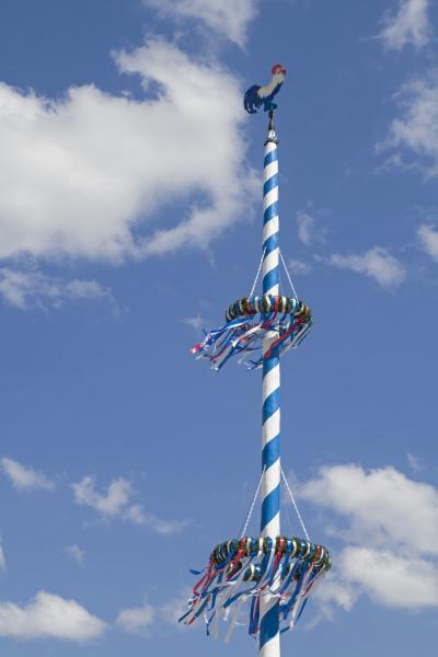bayerischer maibaum vor weissem blauen wolkenhimmel