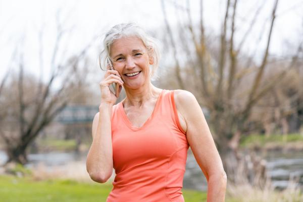 seniorenfrau in sportkleidung die anruf auf