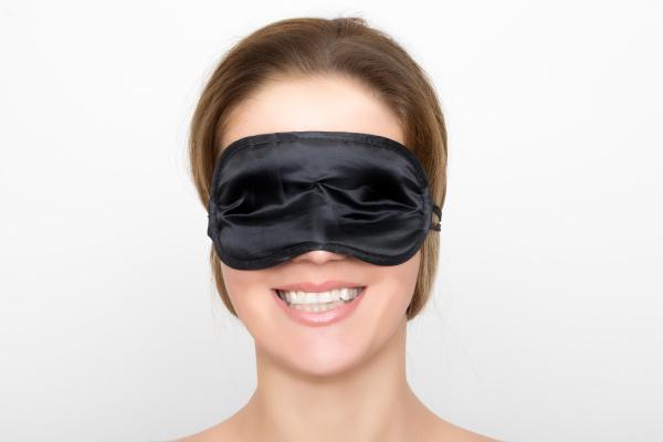 wunderschoene frau mit schwarzer schlafmaske