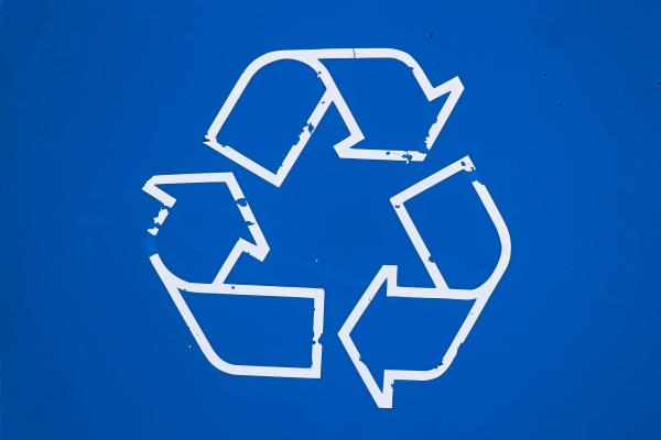 nahaufnahme eines abgenutzten recyclingschildes auf blauem