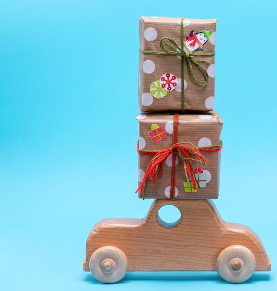 holzkindemaschine traegt geschenke in papier gewickelt