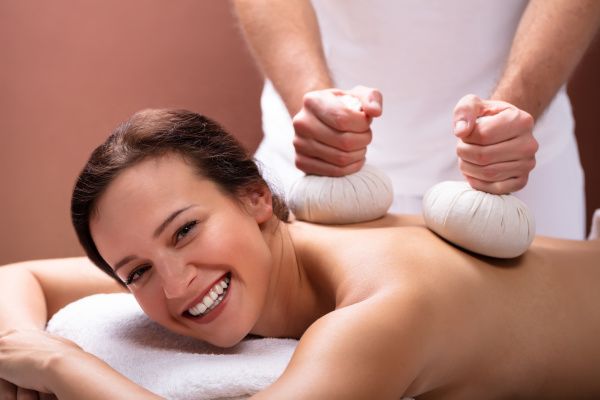 therapeut giving massage mit kraeuterkompressebaellen an
