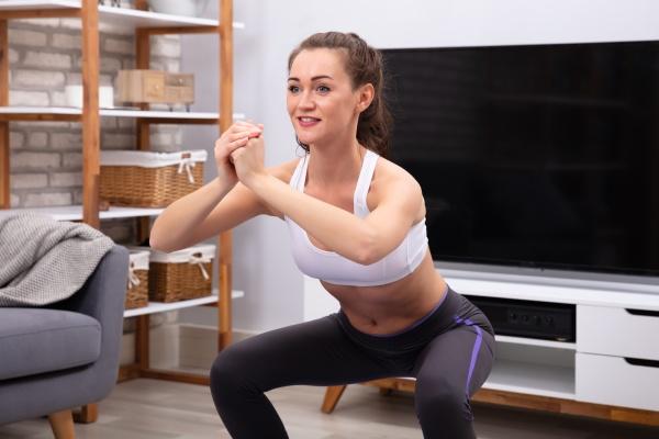 glueckliche frau tun squat UEbung