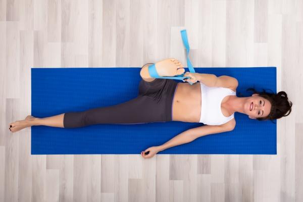 frau nutzt yoga guertel beim UEben
