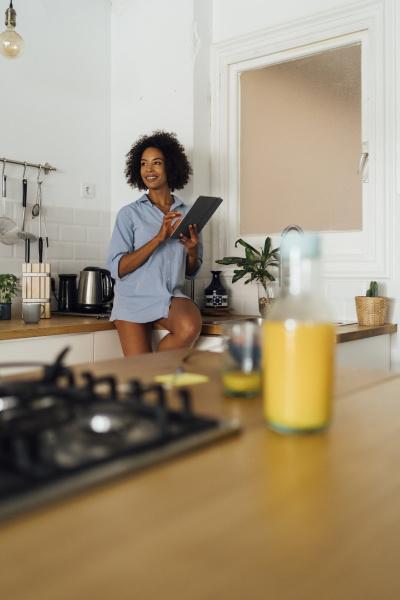 frau, sitzt, auf, arbeitsplatte, ihrer, küche, mit - 26355367