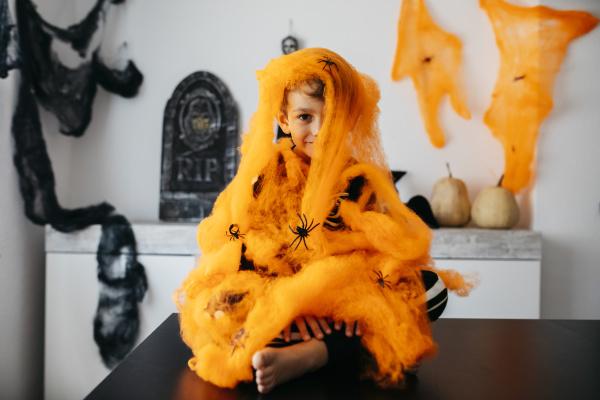 kleiner junge in orangefarbenem spinnennetz an