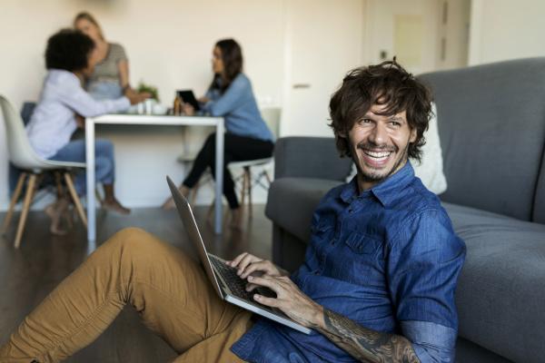 lachender mann sitzt auf dem boden