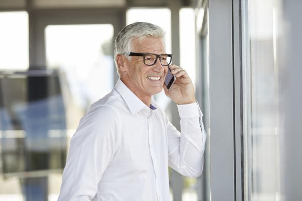 erfolgreicher geschaeftsmann mit smartphone telefonische gespraech