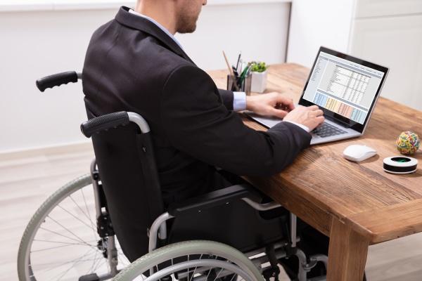 geschaeftsmann sitzt auf rollstuhl mit laptop