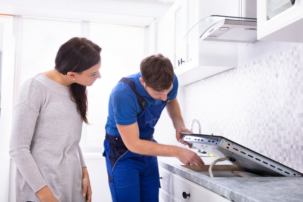 reparaturarbeiter befestigung induktionsherd in der kueche