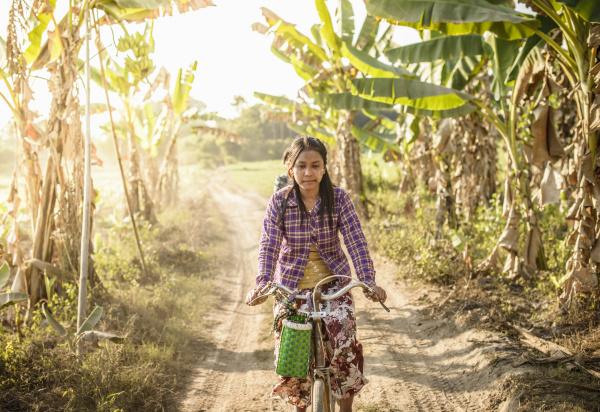 asiatische frau faehrt fahrrad auf landstrasse