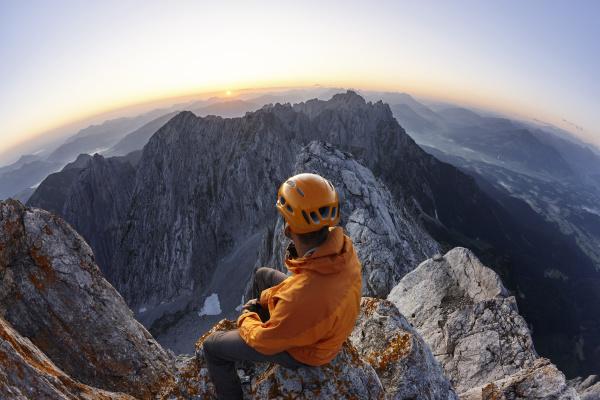 kletterer mit orangefarbenem helm sitzt bei