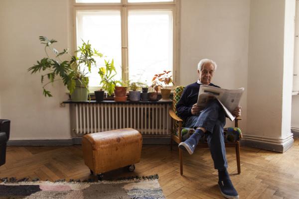senior mann lesen zeitung zu hause