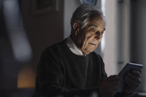 senior mann mit tablet zu hause