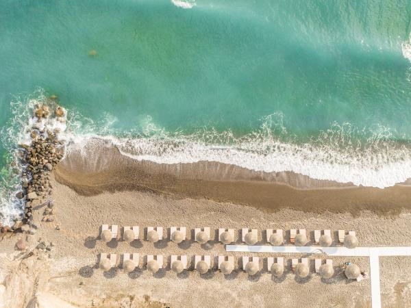 luftaufnahme des strandes mit sonnenschirmen auf