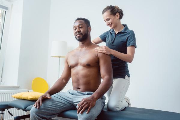 physiotherapeut massiert einen jungen schwarzen mann