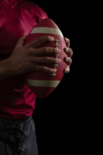 american football spieler haelt einen fussball