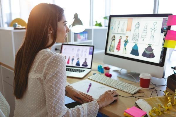 modedesignerin arbeitet am computer am schreibtisch