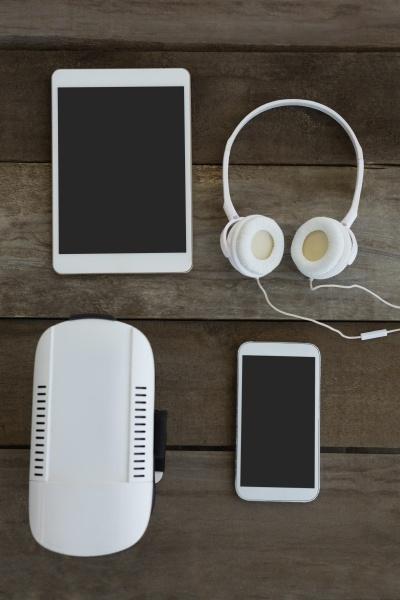 verschiedene elektronische gadgets auf holzoberflaeche