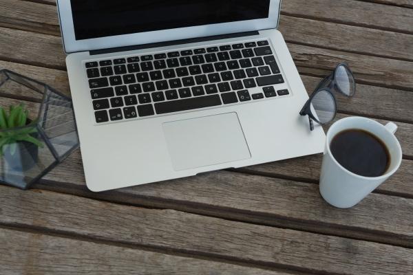 laptop brille schwarzer kaffee und topfpflanze