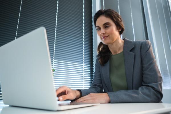 weibliche fuehrungskraft mit laptop am schreibtisch